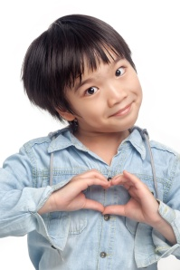 Happy boy making heart hand